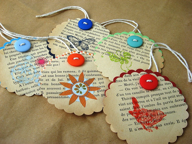 Paper tags- old book pages, stamped with ink and trimmed with buttons