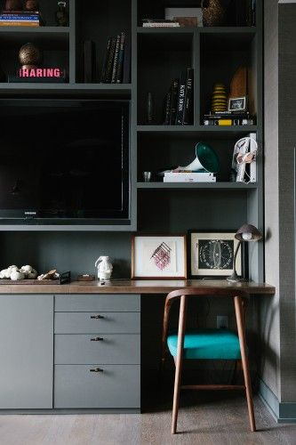 Dark built ins with very stylish desk chair