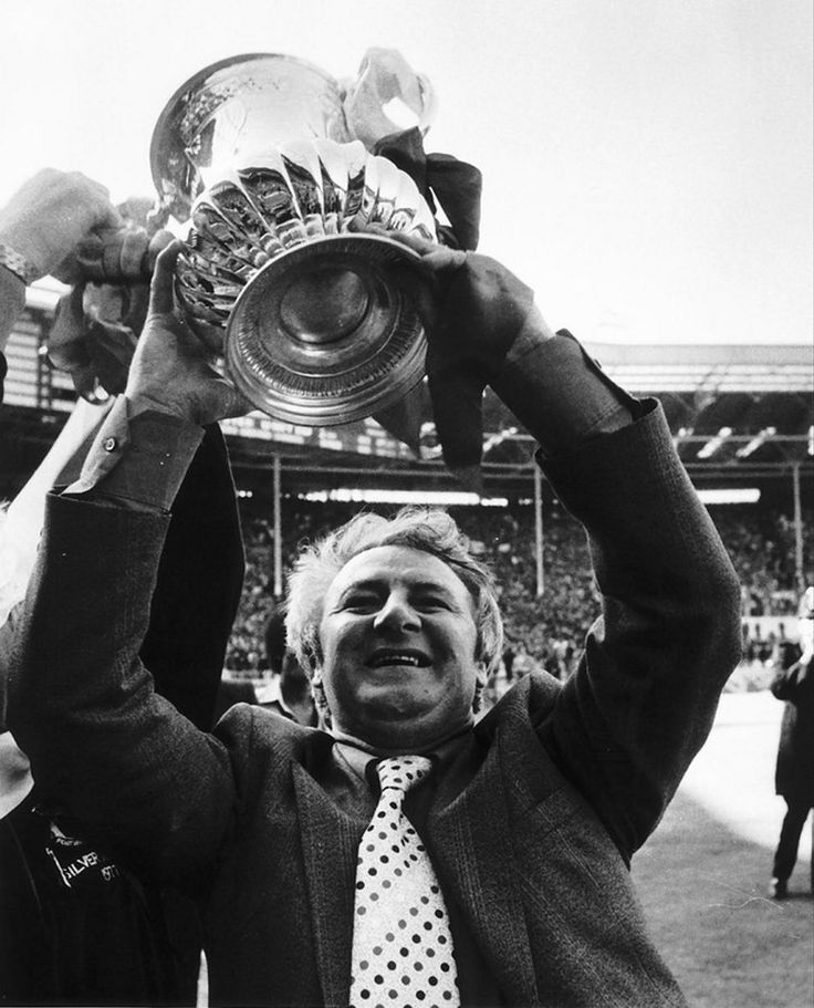 Tommy Docherty lifts the FA Cup in 1977