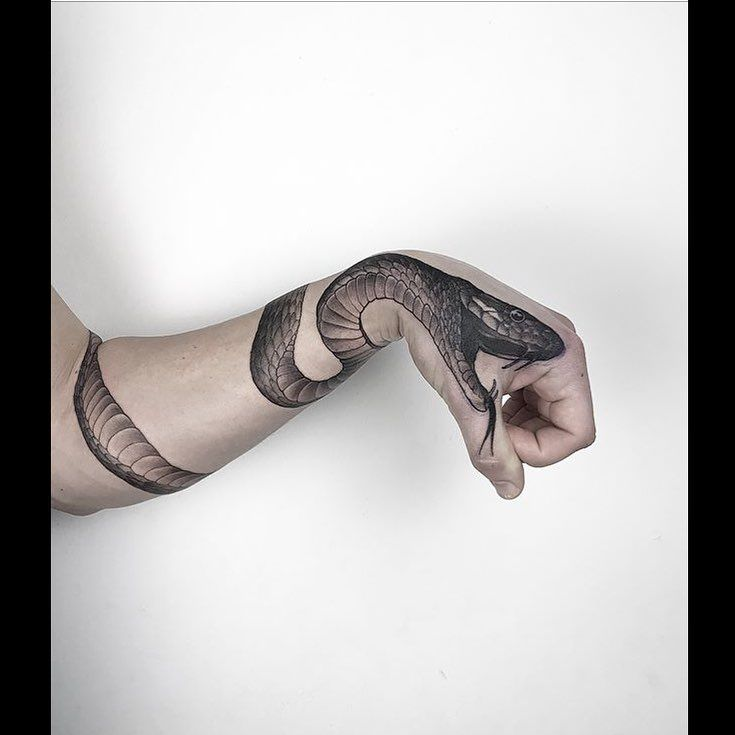 Realistic black snake tattoo inked around the left arm and on the hand