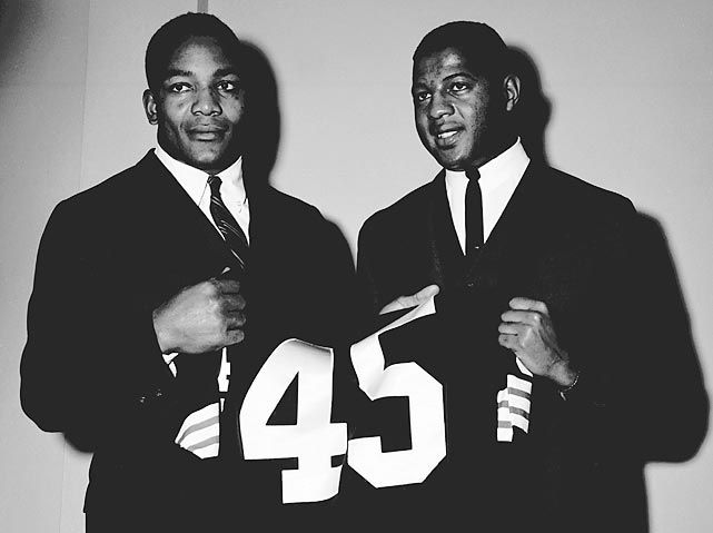Jim Brown & Ernie Davis One became one of the all-time running backs in NFL history. The other was the first African-American to win the Heisman Trophy. And because of a last minute trade orchestrated by Art Modell became a member of the Cleveland Browns however because of contracting Leukemia never played a down for the Browns. What could have been. Mr Davis lost his battle in 1963