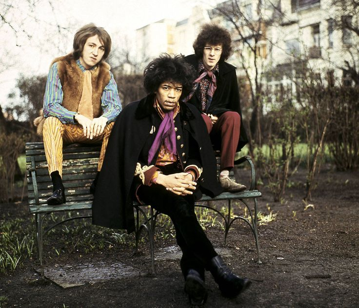 Jimi Hendrix and bandmates Mitch Mitchell and Noel Redding sit on a park bench