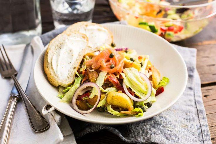 Recept voor maaltijdsalade van gerookte zalm voor 4 personen. Met zout, peper, groene pesto, gerookte zalmfilet, slamelange, paprika, komkommer, rode ui, krieltjes gekruid, yoghurt-mayonaise, kappertjes, afbakstokbrood en roomkaas