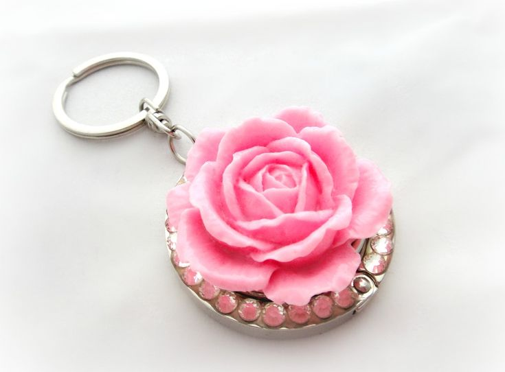 A beautiful women's accessory, a pink rose purse hanger. A sparkly round keychain with Swarovski crystals and a lovely pink rose. It is also a folding purse hook and it can even be used as a bag charm to give a touch of colour to your favourite bag. This charming accessory is perfect for those wh...