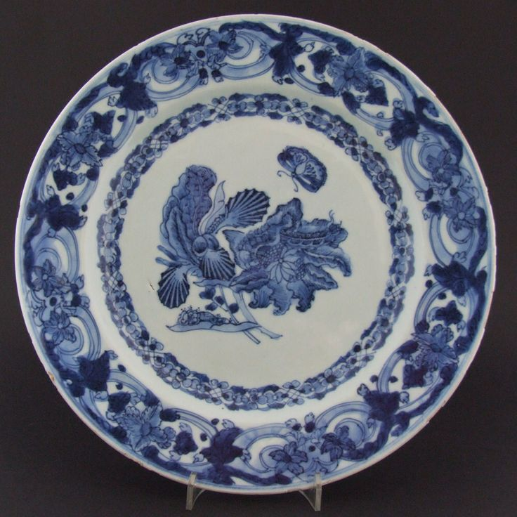 A Blue and White Chinese Export Porcelain Botanical `Merian` Plate c.1740-1750. The Center Painted with a Butterfly or Moth Hovering Over Two Large Caterpillars on a Spray of Iris and Clematis. The Cavetto and Border with Intricate Strapwork Designs.
