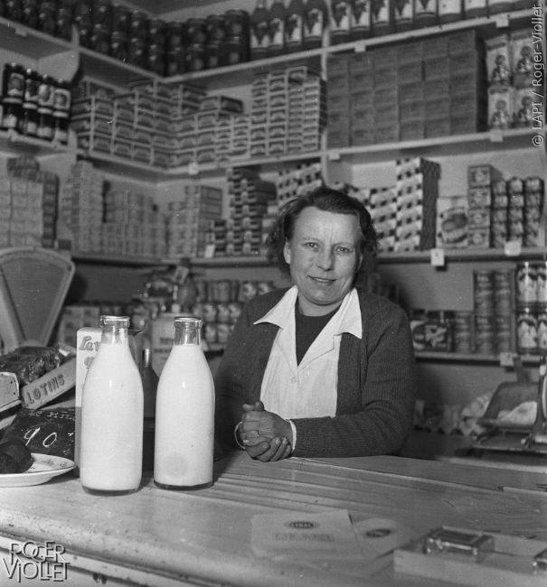 Epicière au comptoir de son magasin. Paris, 1956.