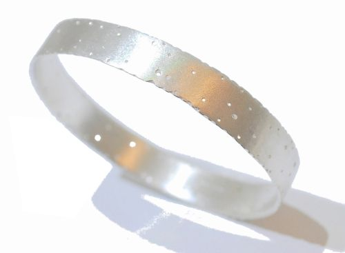 This sterling silver bangle features an exquisite satin finish creating a smart, modern, elegant design that then highlights the textured almost bark like edge and drilled hole detail.  The drilled pattern and edge brings a delicate handmade aspect to the bangle and stops the design looking too solid, this bangle would be perfect for someone with an interest in nature and organic forms.
