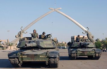 """2003, invasion of Iraq, March 19-May 1: US Army M1A1 Abrams tanks and their crews pose for a photo in front of the """"Hands of Victory"""" monument at Baghdad's Ceremony Square in November 2003."""