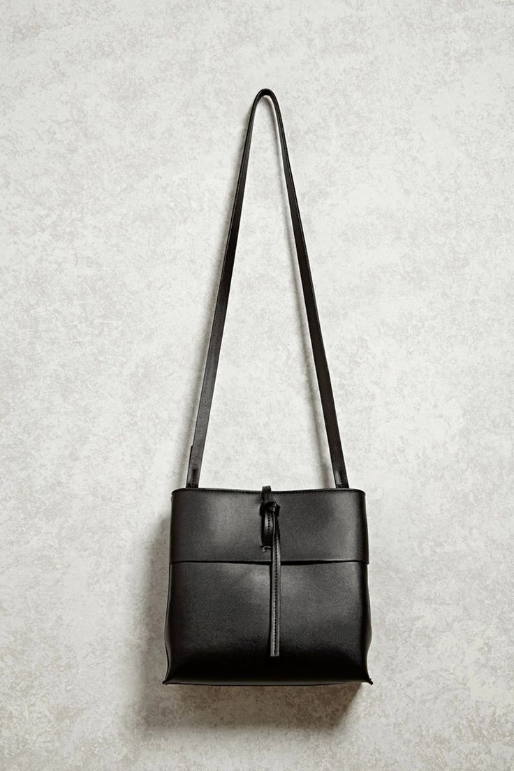 Crafted in a faux leather, this structured bag features a single shoulder strap, a tie-front fastening, top zipper, two interior slip pockets, an interior zip pocket, and topstitched details.