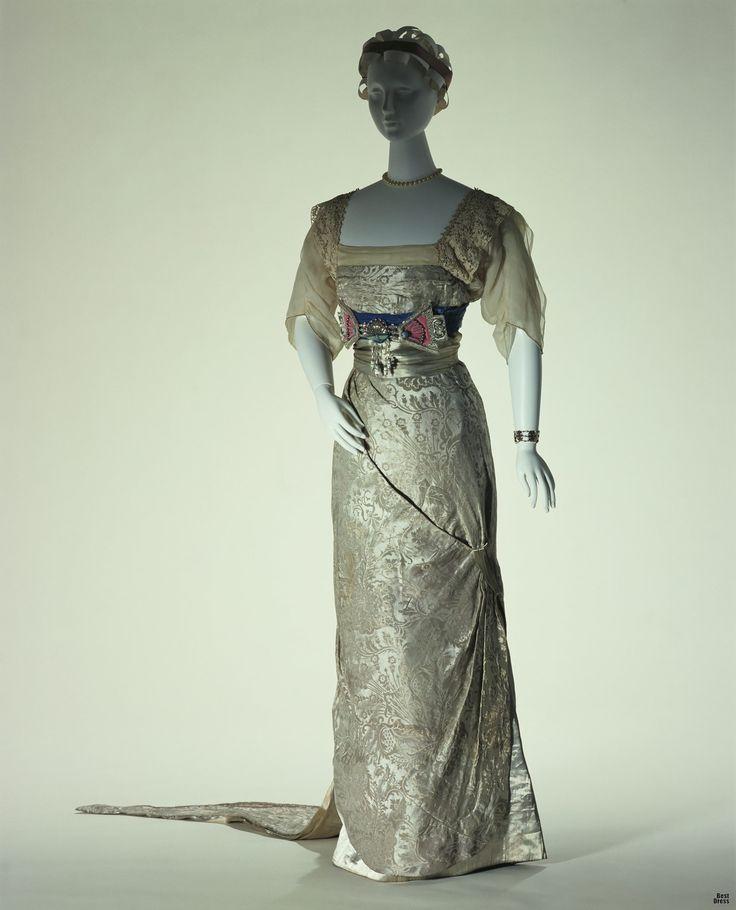 1911г. (зима), Франция  Designer: Jeanne Paquin Brand: Paquin  Вечернее платье в египетской стилистике: стилизованное изображение скарабея на поясе и асимметричная юбка. Это хороший пример восточного влияния на моду, которое ощущалось в то время. Жанна Пакуин завоевал популярность среди женщин высшего общества и актрис, потому что ее платья, которые всегда исполнялись исключительно под заказ, всегда были великолепны и романтичны.