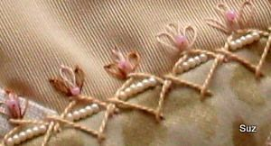 Row of pearls along a seam oversewn with herringbone stitch. Lazy daisy buds with  a centre bead