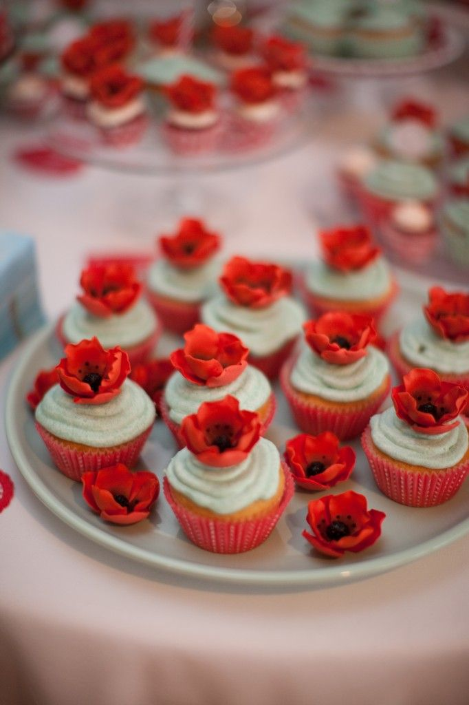 Dessert table with red poppy cupcakes with light blue accents.
