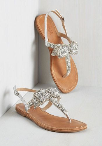 These sparkly sandals from Dolce by Mojo Moxy challenge traditional footwear with their exceptional flair! Taking a classic T-strap silhouette and enhancing it to new heights with a bow detail bedecked with rhinestones, silver beading, and chain link accents, these kicks simply can't be beat.