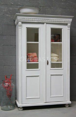 Vitrinekast 10020 - Origineel oude vitrinekast met een grijs witte kleur. De kast heeft een prachtige uitgewerkte koof en sierlijke lijsten naast de deuren. Achter de vitrine deuren zitten drie vaste legplanken.