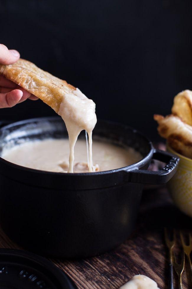 """""""Сырное фондю"""" Для того чтобы приготовить фондю, добавьте нарезанные кубиками сыр гауда и швейцарский сыр в миску и перемешайте с кукурузным крахмалом и перцем. Протрите горшок для фондю чесноком. Налейте в него 1,5 стакана белого сухого вина, столовую ложку коньяка и разогрейте на среднем огне. Когда жидкость начнет закипать, добавьте сыр, медленно помешивая. Приправьте соус мускатным орехом и перцем. Подержите его на медленном огне до готовности.  Подавайте фондю с круассанами или…"""