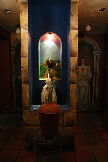 San Miguel Arcangel statue, lit candle offering, vase, red cross nun mural, Hallway decor leading to the facilities, La Fonda de San Miguel Arcangel, (The Fountain of Michael the Archangel), a fine restaurant, Guadalajara, Mexico by Wonderlane, via Flickr