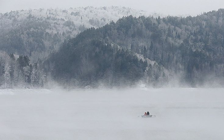 A man and a woman travel in a rowboat along the Yenisei River through a frosty fog in the Taiga district