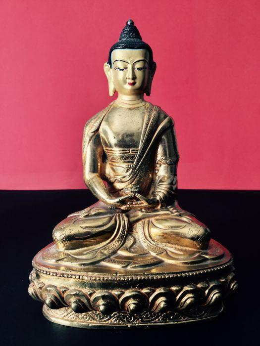 Vertegenwoordiging van Amitabha in koper met goud patina - Nepal - het begin van de 21e eeuw.  Deze stauette werd gemaakt in een werkplaats die is gespecialiseerd in de vervaardiging van objecten in koper die een prachtig resultaat dankzij de verworven vaardigheden levert. Het gezicht is geschilderd in fijn goud. Amitabha is soms verward met de Boeddha Shakyamuni of beschouwd als de grootste van de Boeddha's. Zijn mantra wordt elke dag door praktiserende boeddhisten gereciteerd.Hoogte 205…