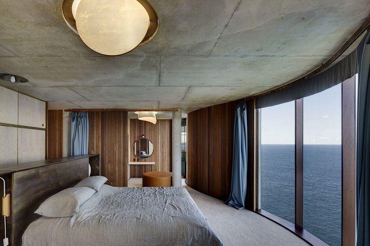 A daring clifftop home in Sydney that is curved in concrete, carved from sandstone and bathed in filtered light.