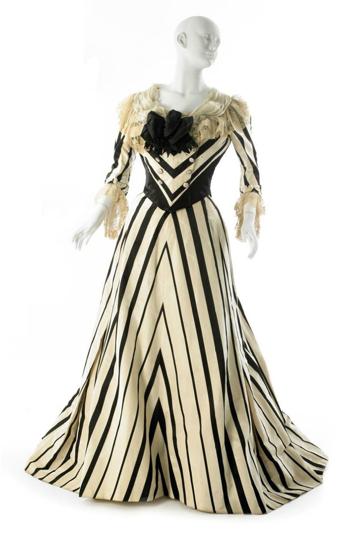 """Worth afternoon dress ca. 1900. Dresses were generally one piece with bodices and skirts sewn together, high boned collars, and a skirt that flared out like a trumpet. Front buttoned closings were also popular on bodices"