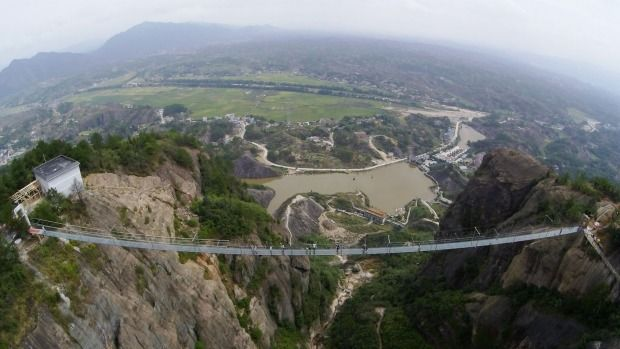 Tourists walk on the suspension bridge made of glass at the Shiniuzhai National Geological Park. Photo: Getty Images