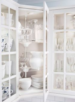 Close-up of cabinets with white glass doors filled with white china and glassware.