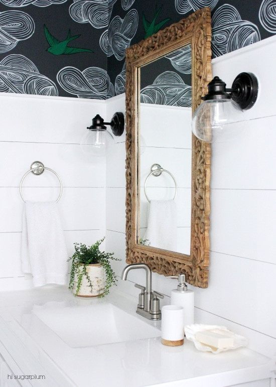 We love this dramatic bathroom remodel. Transform your space with new tiles, a decorative mirror, and unique lighting.