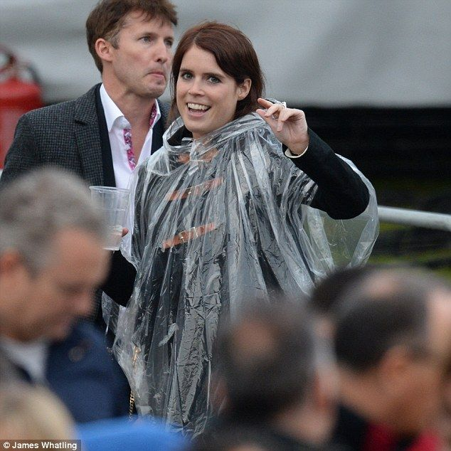 Eugenie opted for comfort over style by throwing a clear plastic poncho over her duffle co...