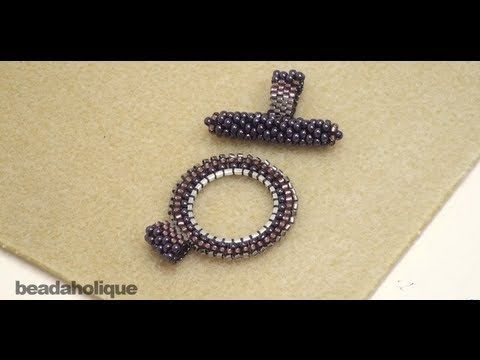 http://www.beadaholique.com/yt - Learn how to bead weave a toggle clasp using a combination of brick stitch and peyote stitch. This round part of the clasp was made using a 20mm Quick Link round but any circular form will do. Three types of beads are used, 2 which are size 11/0 and 1 which is size 15/0. Make a custom toggle to match your bead we...