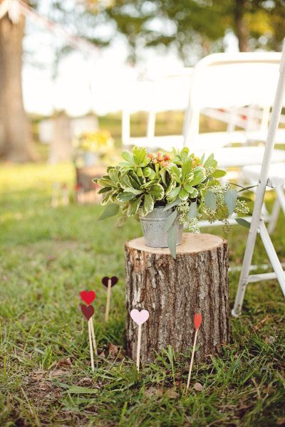 Funky tree stump, potted plant, and hearts-on-a-stick decor for the aisle