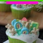 Lucky Charms Cupcakes with Marshmallow Icing & Surprise Filling. Kids LOVE these cupcakes and they are the perfect dessert for St. Patricks day!! Topped with Lucky Charms and a surprise filling inside these will be a huge hit!