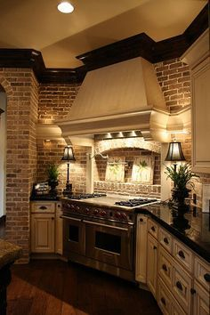 Exposed brick can add character and charm to any kitchen. Love this style featuring dark countertops and crown mouldings!