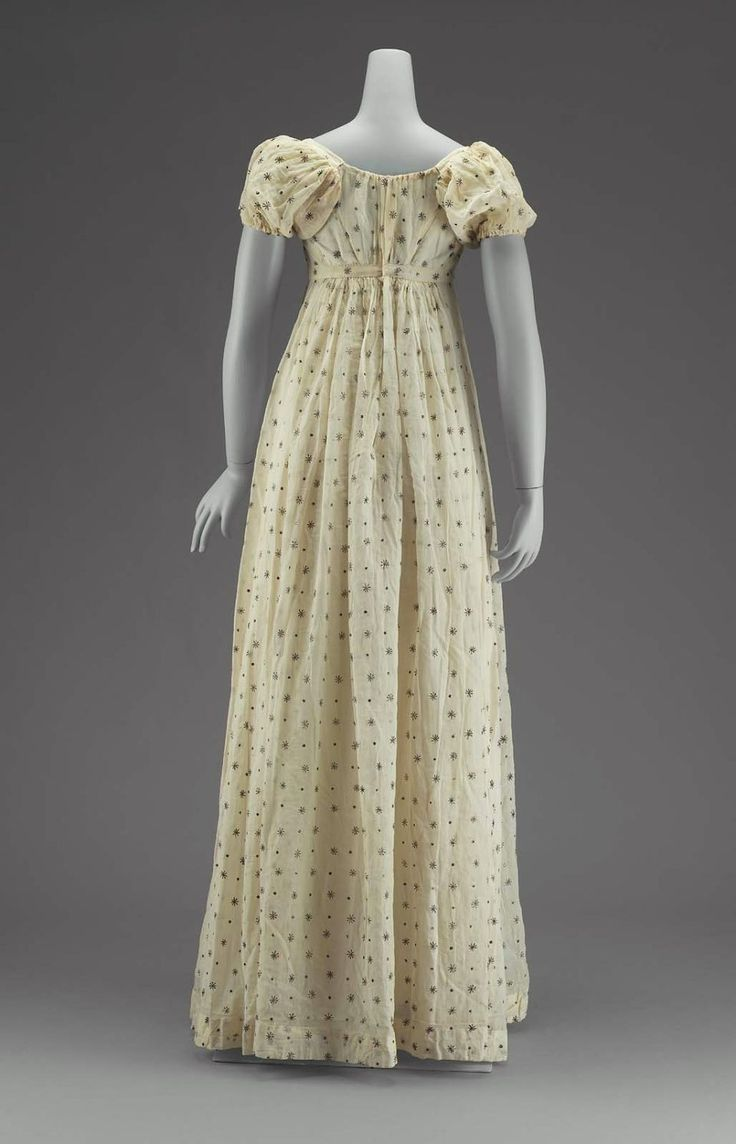 American Federal White Mull Dress of Indian Fabric Circa Early 19th Century. White Mull Embroidered with Silver in a powder of alternating dots and stars; short, high-waisted bodice; short, full sleeves; all fullness of skirt gathered to back. Museum of Fine Arts, Boston, Massachusetts.