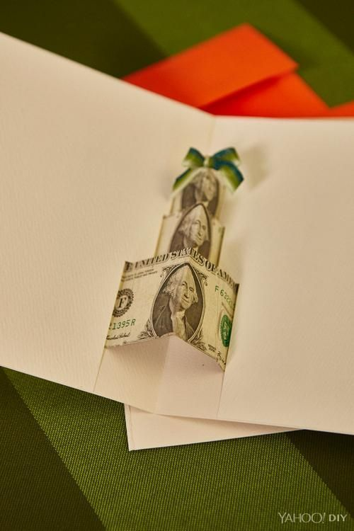 3. From the center crease, leave enough space to make a 'box' shape and then fold the rest of the bill out and away from 'box'. 4. Using small pieces of blue painters' tape position the bills to look like a stack of presents and tape down those outer pieces you just folded out and away to the opened