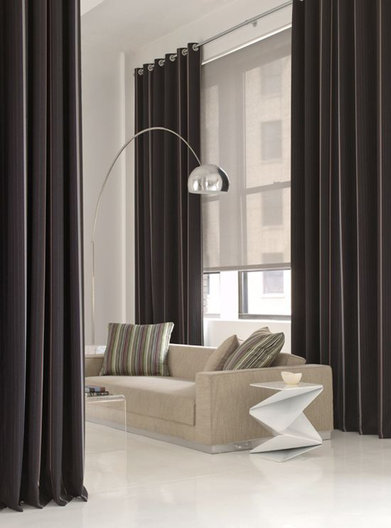 Roller blinds combined with curtains create a modern, functional window treatment
