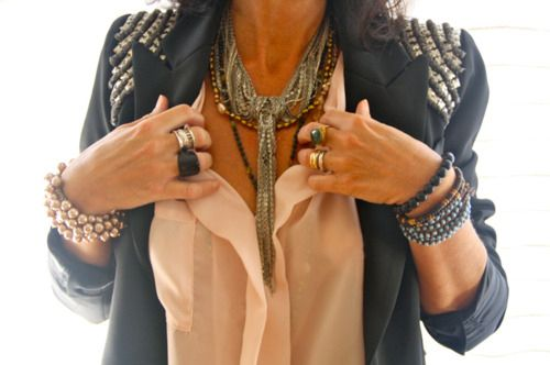 Juxtaposition of classic white shirt, beaded hippy jewels and studded leather jacket. The lady looks so elegant also.