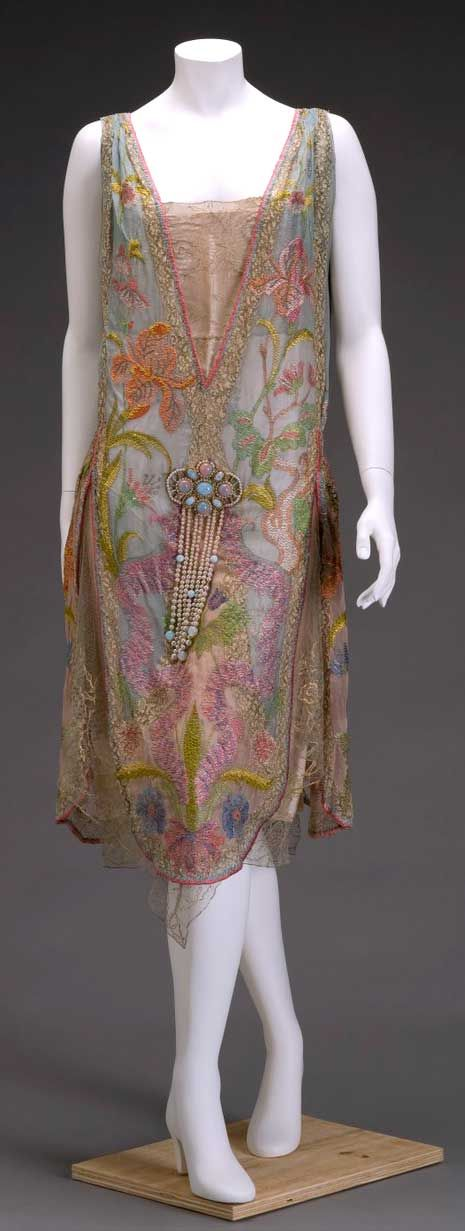 "Callot Soeurs, circa 1926. Silk, silk and metallic lace, and imitation pearls and opals. Indianapolis Museum of Art: ""Irises and water avens adorn this elegant dress. Embroidered layers of soft, sheer, exotic fabrics combined with a large bejeweled ornament in the center typify dresses of the flapper era. ... Callot Soeurs in Paris was famous for the use of exotic fabrics, antique laces, lavish beading, and delicate embroideries."""