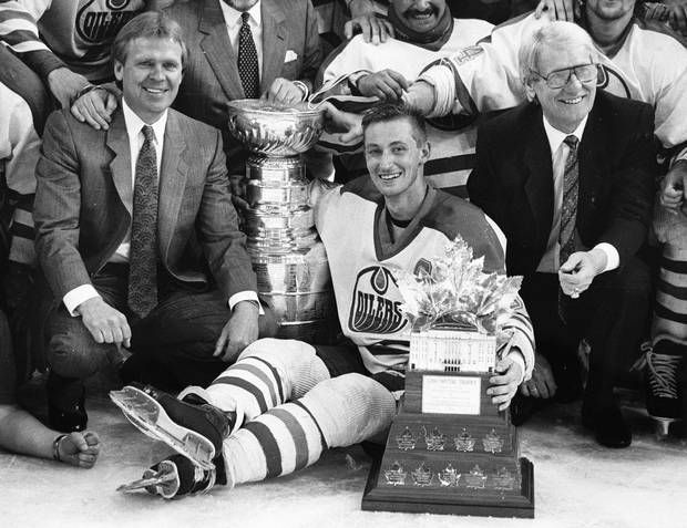 Glen Sather, left, sits with Wayne Gretzky of the Edmonton Oilers on May 26, 1988, after Edmonton defeated the Boston Bruins to win the Stanley Cup. At right is assistant coach John Muckler.