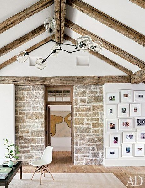 The irregular arrangement of family photos in this living space mimics the lines of the rugged stonework to their left. This home, a farmhouse on Martha's Vineyard, was designed to foster a light and airy feeling, an aesthetic mirrored by the wide, white mats on the photos.