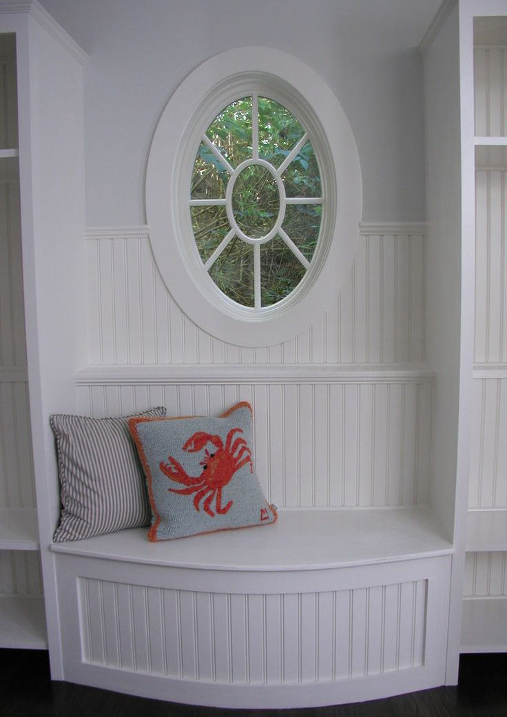 NOOK – custom bench beneath a beautiful oval window seems like a perfect spot to relax.