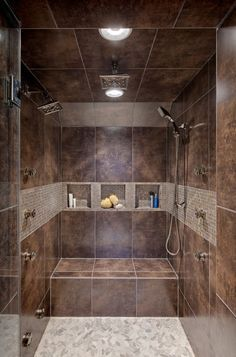 Not a fan of the color but I love the layout of this contemporary steam shower with tons of heads and nozzles plus a bench.