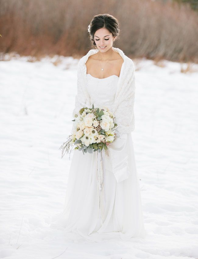 Winter wedding inspiration. Wedding portraits in the snow. Featuring bridal dress and fur shawl by Marisol Aparicio.  Jennifer Fujikawa Photography