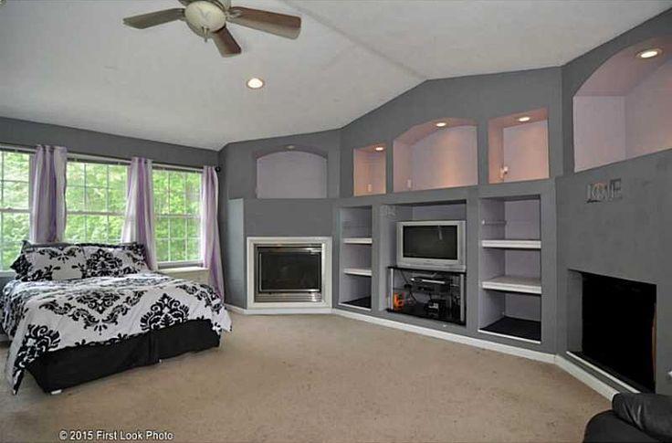 Transitional Master Bedroom with High ceiling, Ceiling fan, metal fireplace, flush light, Carpet, Built-in bookshelf