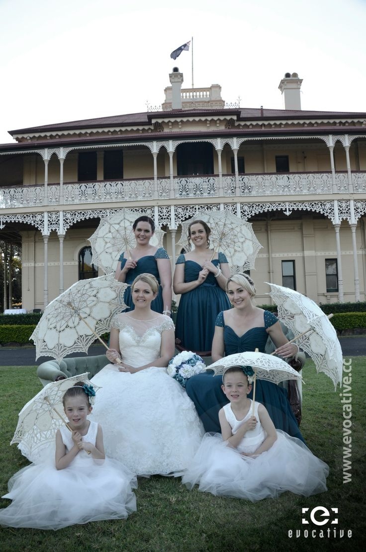 Bride, three bridesmaids and two flower girls, all with parasols (umbrellas), sitting on a classic old lounge in front of the mansion at Woodlands of Marburg. #WeddingPhotography