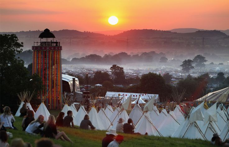 People gather to watch the sunset on a hill above the tipi field as music fans walkthrough the Glastonbury Festival site at Worthy Farm, Pilton on June 24, 2009