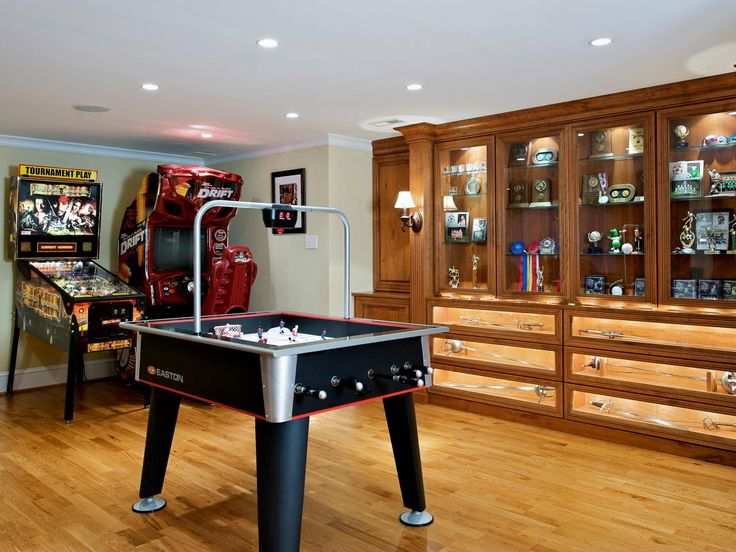 This fun, family game room comes with a custom display case shows off sports memorabilia. A foosball table and arcade-style video games are the main draw in this basement game room, however.