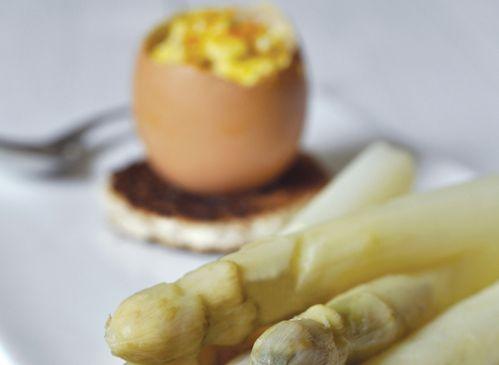 Les ingrédients pour faire la recette aux asperges blanches et œufs brouillés : fromage de brebis, des gros œufs, des asperges blanches, du citron, du beurre, une orange et une demi-baguette.