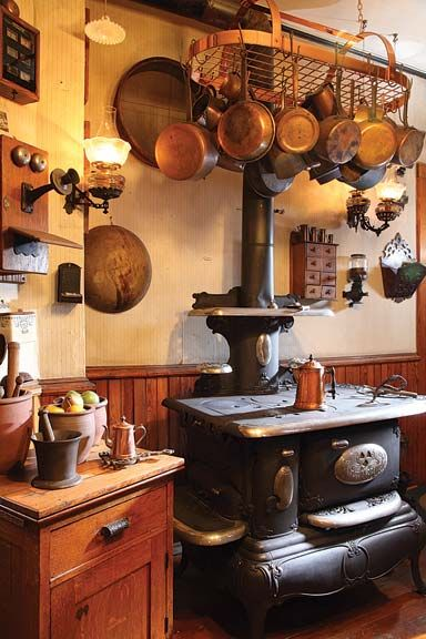 Kitchen, wood cook stove, copper pot rack with copper cookware......and I love the old phone on the wall.
