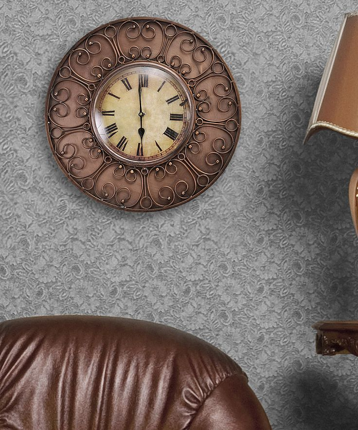 This beautiful wall antique clock features round Iron frame with copper finished in brown. Elegant brown carvings decorate the interior wire frame. The beige clock face give vintage look to your room.