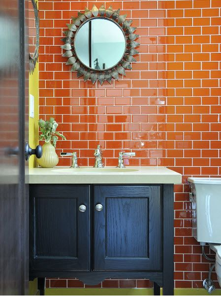 Gorgeous bathroom with lime one lime green wall and one with orange subway tile. Black sink cabinet and lime green baseboards. The mirror would be pretty awesome as a sunburst too.